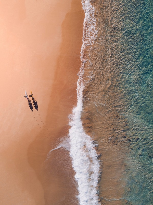 Two surfers walking on the beach